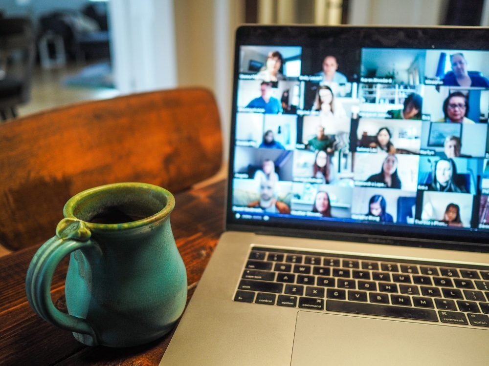 photograph of a laptop being used for a conference call with a mug of tea